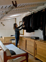 Industrial-style gallery bedroom - woman searching for clothing amongst dark jackets hanging on pole above sideboard next to wooden sofa with pale upholstery