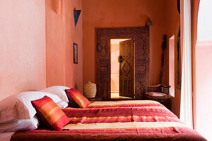 Double bed in Moroccan bedroom decorated in various shades of red