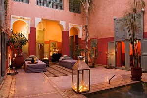 Candle-lit atmosphere in Moroccan courtyard with walls in various shades of red