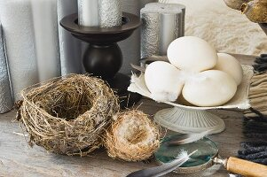 Still-life of various birds' nests and hens' eggs in front of silver ornamental candles