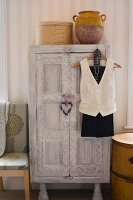 White-washed, vintage wardrobe with carved ornamentation in bedroom