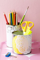 Tin cans decorated with doilies for use as pen pots