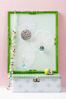 A jewellery holder made from a picture frame and doilies