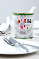 A tin can covered with newspaper and decorated with letters as a table bin