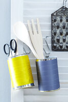 Decorated tin cans being used as storage tins for kitchen utensils hanging on a wall