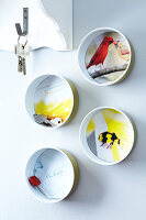 Wall decorations and a key hook made from individually designed tin cans