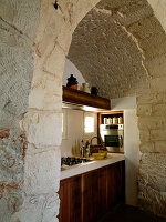 View through stone archway of simple kitchen counter in a Trullo house