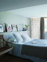 Country-house-style bed with bedspread in front of pictures on masonry shelf