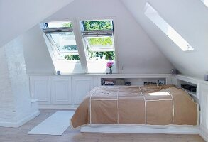 Bed with bedspread in corner of bright attic room with open dormer windows