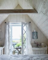 Bed in front of open terrace door in wood-panelled attic room