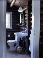 View of modern bathroom in log cabin through open door