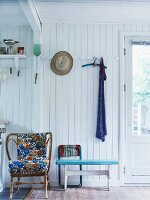 Rattan armchair with colourful cushions against white-painted wooden wall