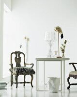 Fur cushion on antique armchair and modern table in white room