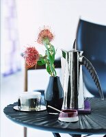 Coffee break - chrome coffee pot and vase with red flower on side table