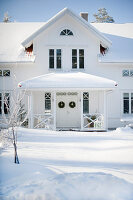 White wooden house with roofed porch in snowy landscape