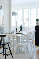 Kitchen table and white, retro-style metal chairs in open-plan interior