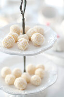 Chocolates covered in dessicated coconut on a tiered cake stand