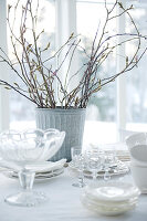 Dishes and glasses in front of metal vase of twigs on table with tablecloth