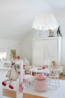 Scandinavian-style child's bedroom - soft toys on white chairs around table in front of white wardrobe