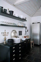 Black and white crockery, glasses and silver candlestick on old chest of drawers below wall mounted shelves and next to stainless steel fridge in loft apartment kitchen