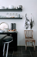 Tea towels with stag motif and old wooden chair next to crockery on wall-mounted shelves; designer bar stools at counter in foreground