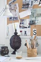 Oriental lantern on desk below pin board on white wooden wall