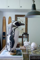 Stuffed penguin on stacked books and board game on table below vintage pendant lamp