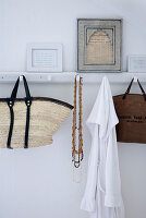 Wicker shopping bag and necklaces hung from vintage-style, white-painted hook rack with framed, written pages on top
