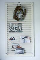 Cowboy hat and brochures hung on white, louvred shutter used as magazine rack mounted on wall