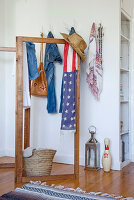 Straw hat and Stars and Stripes scarf on wooden screen in front of white hunting trophies used as coat pegs