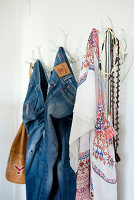 Jeans, necklaces and ethnic scarf hanging from stylised antlers used as coat pegs