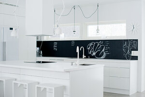 White designer kitchen with black splashback; simple, wood-frame bar stools at kitchen island