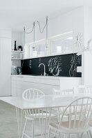 Open-plan designer kitchen in purist white with black splashback and white-painted designer chairs around dining table