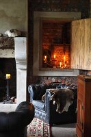 View of lit candles in niche with open wooden door above black leather armchair in rustic room with open fireplace