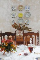 View across festively set table to wall plates mounted on plastered wall