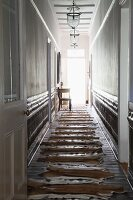 Animal-skin rugs laid out on wooden floor in narrow hallway