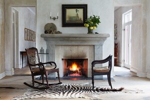 Vintage rocking chair and antique armchair on zebra-skin rug in front of open fire in simple house
