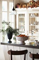 Olive branches, fruit and liqueur on counter in Provencal kitchen
