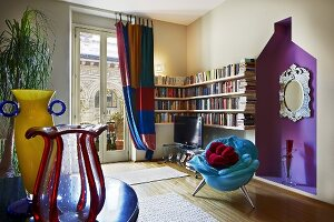 Modern living room with postmodern highlights - blue plush armchair in front of purple niche and colourful glass vases on table