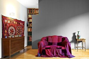 Brightly coloured throw on sofa in front of grey-painted partition in modern living room with traditional ambiance