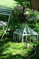 Cold frame next to garden chair and antique-style metal elements for guiding garden hose