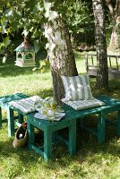 Seating area with striped cushions on small, green wooden bench against birch tree