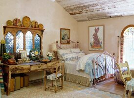 Charming art noveau style bed next to an antique wall table in front of a traditional country home window in the attic bedroom