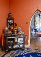 A wooden stove which has been converted to a china cupboard in front of an orange wall with a pointed arch passageway