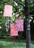 Accordion lanterns decorated with ribbons hanging from tree