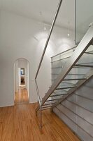 Stainless steel staircase next to glass and steel installation in interior with arched doorway and traditional ambiance
