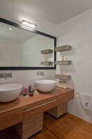 Minimalist designer bathroom with white ceramic basins on wooden counter and wall-mounted mirror