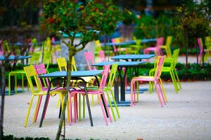 Cafe with outdoor seating - tables and multi-coloured garden chairs on gravel surface