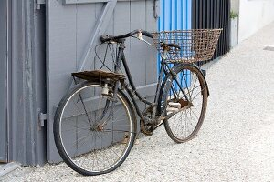 Rusty vintage bicycle leaning on wooden gate