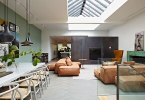 Modern interior with classic chairs in dining area and comfortable floor cushions in lounge area below skylight